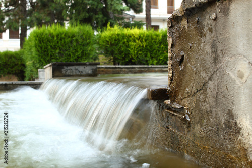 Poster Watervallen Cascade of a small decorative waterfall of the fountain in a park. Long exposure time