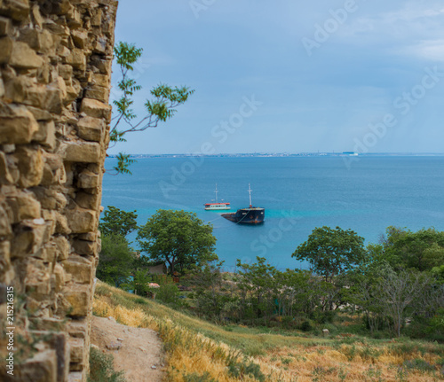 Spoed Foto op Canvas Schipbreuk Sunken ship off the shore on which there is a stone fortification wall