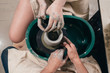Man and woman hands pottery studying in studio. Creating vase. Hands in the clay and the potter's wheel with the product. Pottery class from above.