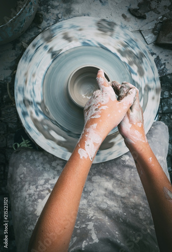.Potter wheel and child hands making a bowl. Top view vertical image