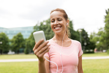 Fitness, Sport And Healthy Lifestyle Concept - Smiling Woman Listening To Music On Smartphone At Park