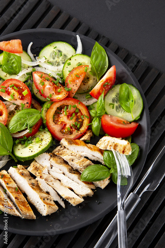 Vegetable salad and grilled chicken on a black background. Healthy food. Diet. Vertical.