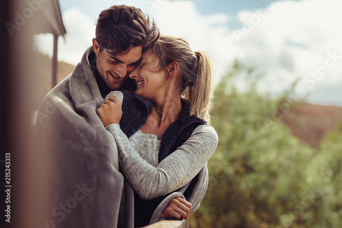Leinwand Poster Romantic couple wrapped in blanket outside