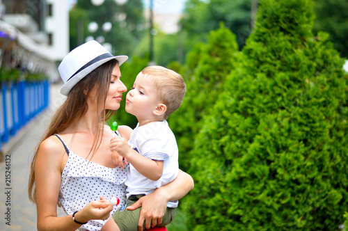 Fotografia  A young beautiful mother in a white hat is holding a two-year-old son and they are eating colored lollipops