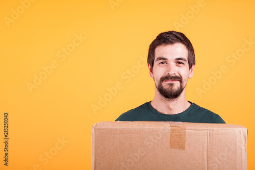 Portrait of handsome young man holding a box in his hands Fototapeta