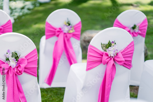 Obraz na plátně Wedding chairs, spandex white cover chairs, pink organza sash with cone of flowe