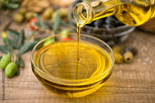bottle olive oil of pouring in glass bowl.