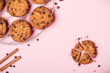 Whole And Broken Chocolate Chip Cookies And Crumbs On Pink Background