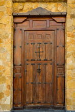 Weathered Plank Wood Entrance Door Of Residential House Mansion Villa With Wrought-iron Hinges Latches. Dark Brown Earthy Color. Grungy Aged Texture. Backdrop Wallpaper. Hacienda Style