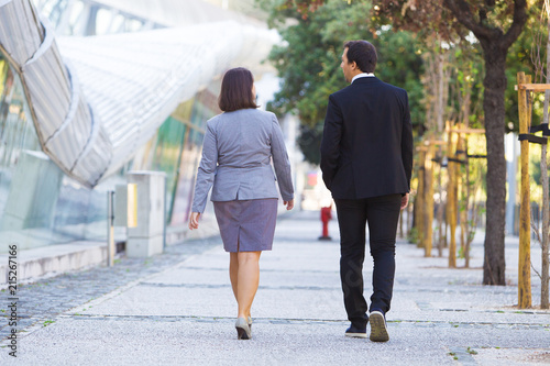 Foto Confident business colleagues in formal suits going to office over city street