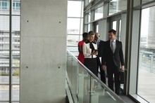 Group Of Business People Having A Discussion While Walking In