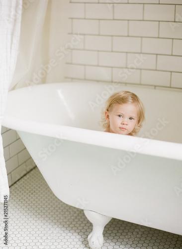 baby in bubble bath in white bathroom