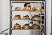 Baker Standing Behind Trays Of Fresh Baked Bread