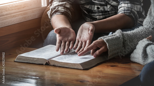 Fotografia Two christianity sitting around wooden table with open holy bible and reading