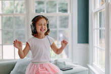 Cute Young Girl Listening To M...