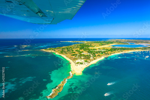 Aerial view of Rottnest Island in Australia. Scenic flight with wing of plane over famous tourist destination of Western Australia. Rottnest Island is located near Fremantle and Perth.