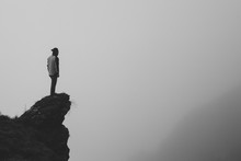 Black And White Image Of A Man Standing At The Edge Of The Cliff Against A Foggy Landscape.