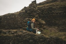 Female Hiker Sitting On The Abandoned Stone Wall