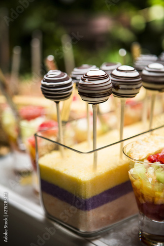 Close-up of Chocolate Lollipops and Glasses of Fruit Cocktail on Dessert Table