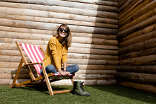 Young Blonde Woman Relaxing On The Wooden Chair