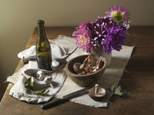 Wild Mushrooms And Garlic On Table With Wine And Flowers