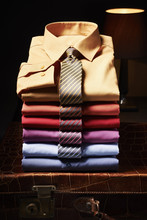 Stack Of Shirts With Ties On Suitcase In Studio