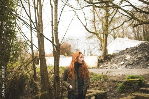 Red hair female hiker looking around in the forest