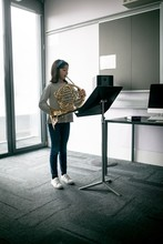 Schoolgirl Playing French Horn...