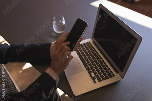 Businesswoman using smartphone while working on laptop