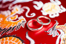 Close-up Of Wedding Rings On Traditional Chinese Printed Fabric