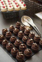 Chocolate Cupcakes Topped With Coffee Beans On Dessert Table At Wedding Reception