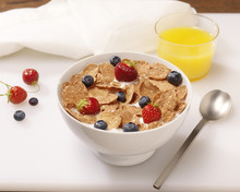 Bowl Of Cereal Flakes With Berries And Orange Juice