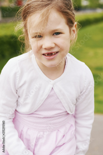 Portrait of 5 year old girl in pink dress and white sweater, smiling and looking at camera showing her front teeth missing