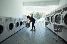 Woman Using Washing Machine At Laundromat