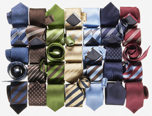 Group Of Multi Coloured Neckties Roled-up On White Background