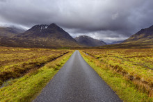Road With Mountains In The Highlands At Glen Coe In Scotland, United Kingdom