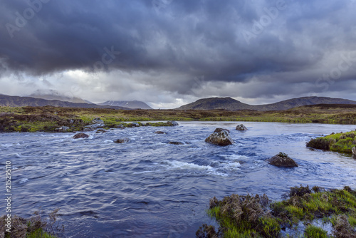 Deurstickers Landschappen River in moor landscape with dark storm clouds with mountains in the background at Rannoch Moor in Scotland, United Kingdom