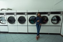 Woman Using Her Phone While Waiting At Laundromat