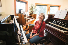 Happy Mature Woman Playing Piano And Organ In Home Studio