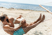 Couple Of Lovers Kissing And Resting In Hammock On Beach Near The Sea
