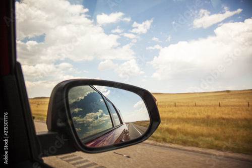 Fototapeta Reflection of sky and clouds in car passenger side window obraz