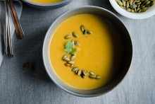 Pumpkin Soup Garnished With Pumpkin Seeds And Sage Leaves