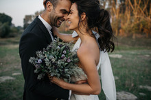 Bride And Groom Embracing In Field At Sunset