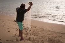 Fisherman Fishing On A Beach