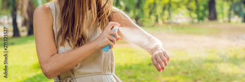 Woman spraying insect repellent on skin outdoor BANNER, long format Fototapeta