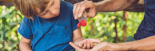 Fotomural Father and son using wash hand sanitizer gel in the park before a snack BANNER,