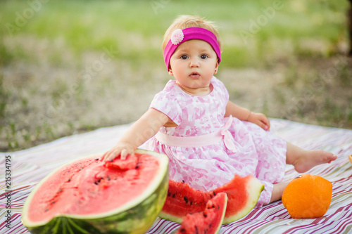 Baby girl on picnic. eating fruits outdoors. Childhood. Canvas Print