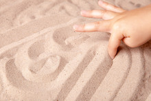 Child Draws A Finger On The Sand