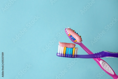 Fotografia  Toothbrushes with paste on color background, closeup