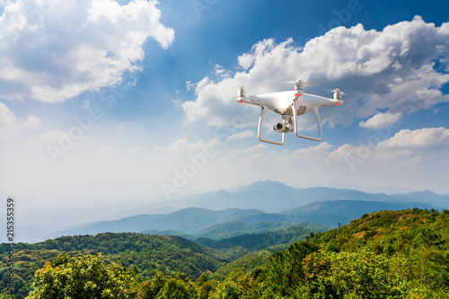 flying drone above green mountain